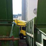 Hinter den Entsorgungscontainern ist die Abfahrt des erste Umzugswagens zu beobachten.